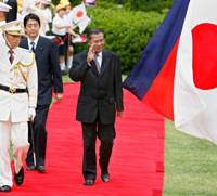 Cambodian Prime Minister Hun Sen, escorted by Prime Minister Shinzo Abe, waves during a welcoming ceremony Thursday at the Prime Minister's Official Residence in Tokyo. | POOL PHOTO