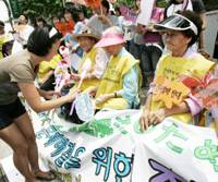 A student presents flowers to former Korean 'comfort women,' who served as sexual slaves for the Imperial Japanese Army during the war, as they shout slogans during a rally Wednesday in front of the Japanese Embassy. | AP PHOTO