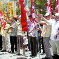 Protesters demand Friday in Naha that the government retract its instruction to revise history textbooks to downplay the military's role in ordering mass suicides in the prefecture during the war. | KYODO PHOTO