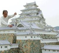 Hiroyasu Imura works on his Himeji Castle replica in the backyard of his home in Enza, Mie Prefecture. | KYODO PHOTO