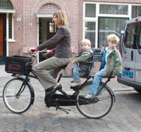 Femke De Vries, bicycling with her sons, Bink, 2, and Vosse, 5, in Haarlem, Netherlands, works a three-day, 25-hour week and spends the rest of her time at home.   SETSUKO KAMIYA PHOTO