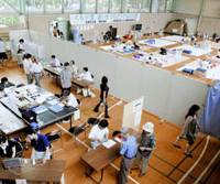 A partition separates voters in Sunday's House of Councilors election (foreground) and evacuees from the July 16 earthquake who are taking shelter at the Hisumi Community Center in Kashiwazaki, Niigata Prefecture. | KYODO PHOTO