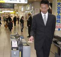 A man goes through a ticket gate at JR Omiya Station in Saitama by touching a Pasmo card to an electronic reader in a demonstration before the card's March 18 debut. | KYODO PHOTO