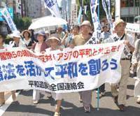 People who lost relatives in the war and oppose politicians' visits to Yasukuni Shrine march Wednesday near the controversial shrine in Chiyoda Ward, Tokyo, to promote peace in Asia and protection of the Constitution's Article 9. | SATOKO KAWASAKI PHOTO