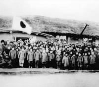 Japanese settlers pose for a photo outside an elementary school that opened in 1943 in the Manchukuo puppet state in northeast China. Noriko Suzuki can be seen beneath the flag, indicated by an arrow. | PHOTO COURTESY OF NORIKO SUZUKI