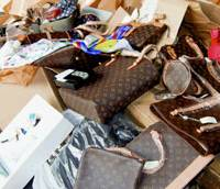 Counterfeit brand items seized by Tokyo Customs are displayed to the media in June. Japan seized a record number of such goods in the first half of this year. | KYODO PHOTO