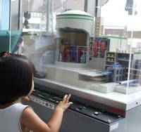 A girl presses a button to light up the model of the Monju fast-breeder reactor at the Aquatom science museum in Tsuruga, Fukui Prefecture. | ERIC JOHNSTON PHOTO