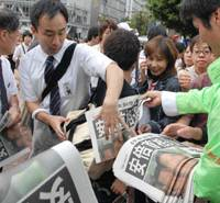 People grab newspaper extras near JR Shibuya Station on Wednesday announcing Prime Minister Shinzo Abe's intention to resign. | YOSHIAKI MIURA PHOTO