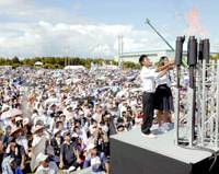 Students light the 'fire of peace' at a park in Ginowan, Okinawa Prefecture, during a rally Saturday to protest a central government directive requiring publishers of history textbooks to alter their descriptions of the Japanese military's involvement in ordering mass suicides of civilians during the Battle of Okinawa.   KYODO PHOTO