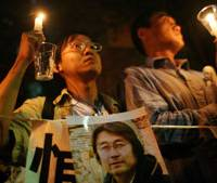 Protesters hold candles and a portrait of slain journalist Kenji Nagai as they gather outside the Myanmar Embassy in Shinagawa Ward on Sunday night. | AP PHOTO