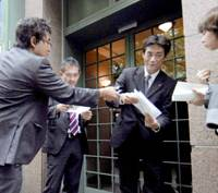 A Nova official distributes statements to reporters Friday morning in front of a building in Osaka's Chuo Ward that houses the language school chain's headquarters. | KYODO PHOTO