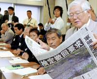 An Okinawa resident, part of a group of political leaders and activists from the prefecture, reads out a newspaper report at a textbook publisher's office in Tokyo about the Sept. 29 rally in Okinawa protesting the government's March textbook screening order. | KYODO PHOTO