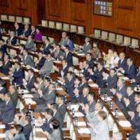 Opposition Party lawmakers applaud after the opposition-sponsored bill on the use of pension premiums was passed Friday in the House of Councilors in a vote of 132-95.   KYODO PHOTO