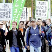 Nova Corp. teachers march Thursday toward Osaka City Hall, demanding that the city help them and the failed foreignlanguage school chain'sstudents. | KYODO PHOTO