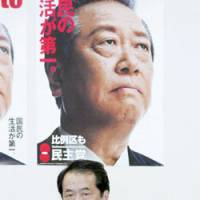 Naoto Kan, deputy chief of the Democratic Party of Japan, appears grim Monday at the party's Tokyo headquarters below a poster of DPJ President Ichiro Ozawa. | KYODO PHOTO
