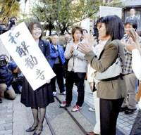 A supporter for plaintiffs infected with hepatitis C through tainted blood products holds a banner reading out-of-court 'settlement recommended' outside the Osaka High Court on Wednesday. | KYODO PHOTO