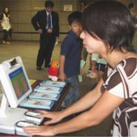 A woman tries out a fingerprint scanning machine during an open house at the Justice Ministry in October. The machines will be installed at immigration control points at ports and airports throughout the country Nov. 20. | SETSUKO KAMIYA PHOTO