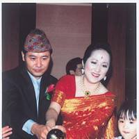 Kazuko Tanikawa, dressed in a traditional Nepalese costume, lights a candle with her husband, Praveen Lama, during their wedding reception in Tokyo on July 13, 2003. | PHOTO COURTESY OF LAMA & TANIKAWA