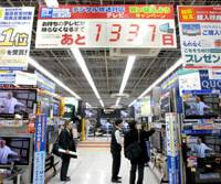 A countdown sign in the Bic Camera store in Yurakucho, Tokyo, last month pitches TV sets compatible with terrestrial digital broadcasting. It reads: 'TVs you have now will be out of use in 1,337 days.'   YOSHIAKI MIURA PHOTO