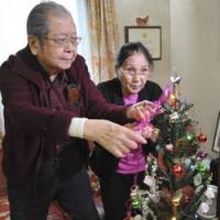 Warren Nobuaki Iwatake and his wife, Emiko, put the final touches on an artificial Christmas tree in their Tokyo home earlier this month. Iwatake's family has brought the tree out every Christmas for the past 70 years, even when that meant risking arrest. | AP PHOTOS