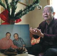 Warren Nobuaki Iwatake shows his family's artificial Christmas tree and a 2002 photo of him with former U.S. President George Bush at his home in Tokyo on Dec.
