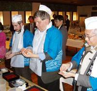 Reporters from Britain and Thailand practice making sushi at a restaurant during a foreign press tour in mid-December. | KAHO SHIMIZU PHOTO