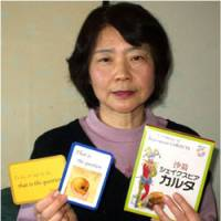 Ayako Yoshimi proudly holds a deck of her Shakespeare 'karuta' cards and a quote from 'Hamlet' at her home in Yokohama last week. | JUN HONGO PHOTO