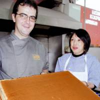 Paulo Duarte and his wife, Tomoko, show off a castella sponge cake at their Lisbon confectionery. | KYODO PHOTO