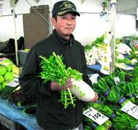 Kaneo Yamamori, who heads a movement against Kamakura's plans to establish a food waste processing plant in the midst of local farms, boasts a Miura daikon at the public market. | ERIC PRIDEAUX PHOTO