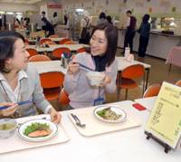 Pola Orbis employees Mikiko Matsumoto (left) and Kyoko Hara eat a Table For Two lunch in the company's cafeteria at its head office in Tokyo on March 7. | YOSHIAKI MIURA PHOTO