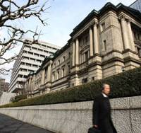 A pedestrian walks past the Bank of Japan headquarters in Tokyo in January. | BLOOMBERG PHOTO