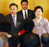 Diplomatic visit: South Korean President Lee Myung Bak and his wife, Kim Yoon Ok, are welcomed by Korean residents of Japan at a reception in Tokyo on Sunday. | AP PHOTO