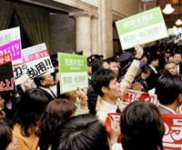 Protesting in vain: Democratic Party of Japan lawmakers protest the ruling bloc's move to reinstate provisional rates on gasoline and other car-related taxes, with some holding signs calling for a snap election, in the Diet on Wednesday. | KYODO PHOTO