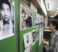 Fighting the good fight: Hideko Hakamada, sister of death-row inmate Iwao Hakamada (seen at left on the wall), looks at family photos in a Tokyo gym during a special charity event in January to free the former featherweight boxer. | AP PHOTO