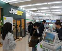 Extended family: Customers shop at a new FamilyMart convenience store that also houses a Subway sandwich outlet in Chiyoda Ward, Tokyo, on opening day, April 30. | KAZUAKI NAGATA PHOTO