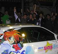 Automotive mascot: 'Itasha' owners pose behind a car decorated with a color sticker of teenage character Nanoha Takamachi from the animated TV series 'Magical Girl Lyrical Nanoha,' on a street in Tokyo's Akihabara district earlier this month. | MINORU MATSUTANI