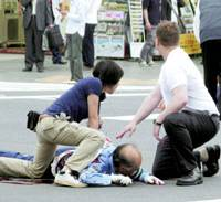 People attempt to help a traffic police officer injured during a stabbing spree in Tokyo's Akihabara district today. Seven people died and 11 were injured after a 25-year-old man from Shizuoka Prefecture began indistriminately stabbing people around 12:30 p.m. | KYODO PHOTO