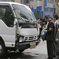 Investigators survey the rented truck that Tomohiro Kato was driving when he crashed into pedestrians in Tokyo's Akihabara district. | KYODO PHOTO