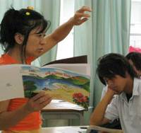 Preserving history: English teacher Chie Miyagi teaches students about wartime mass murders and suicides on Okinawa using her picture book, 'A Letter from Okinawa,' at Haebaru High School in Okinawa this month. | KYODO PHOTO
