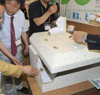 Final carbon footprint: Yukihiro Masuda of Tri-Wall K.K. shows the firm's 'ecoffin' made of special corrugated cardboard during the Funeral Business Fair last month at the Pacifico Yokohama convention center. | SATOKO KAWASAKI PHOTO