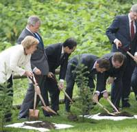 Leaving legacies: (From left) German Chancellor Angela Merkel, U.S. President George W. Bush, Prime Minister Yasuo Fukuda, French President Nicolas Sarkozy, Russian President Dmitry Medvedev and Canadian Prime Minister Stephen Harper stage a tree planting ceremony Tuesday in Toyako, Hokkaido. Below: Clad in traditional Ainu garb, Fukuda's wife, Kiyoko, smiles with Tadashi Kato, chief of the Ainu Association of Hokkaido, Canadian first lady Laureen Harper, British first lady Sarah Brown, and Margarida Sousa Uva, wife of EU Commission Chairman Jose Manuel Barroso, at the G-8 International Media Center in Rusutsu. | AP PHOTO, KYODO PHOTO