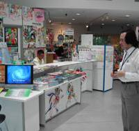 Business promotion: Tokyo Anime Center spokesman Koji Senda, above left, faces the reception desk at the center in Tokyo's Akihabara district on Tuesday, while Jane Fong, CEO of GI Jane Inc., poses next to one of the animation figures on display there.   MINORU MATSUTANI PHOTOS