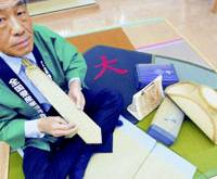 New out of old: Koichi Kanbe, chairman of the Japan Tatami Industry Promotion Association in Kyoto, shows off a tatami tie, bag, hat and other products. | KYODO PHOTO