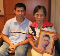 War-separated: Japanese-Filipino Gloria Fuji Mangao, 76, poses with her grandson, Arnel Peres, 40, in a hotel room in Tokyo. In her hands is a photo of her father, Hino Fuji. | KYODO PHOTO