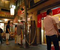 Visitors to the Shin-Yokohama Raumen Museum in Yokohama check out ramen shops on a re-created 1958 street. Below, a bowl of soy sauce-flavored ramen is served at the restaurant Daigen in Minato Ward, Tokyo. | KAZUAKI NAGATA, YOSHIAKI MIURA PHOTOS