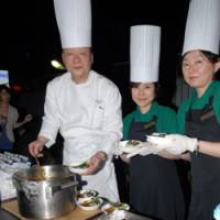 Chow time: Shoji Hirota, executive chef at Hotel Seiyo Ginza, serves curry made for a harvest festival at the Matsuya department store in Tokyo's Ginza district, with two Matsuya employees.