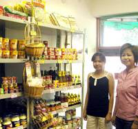 Adobo anyhow: Rosemarie Salvio (right), a longtime Filipino resident in Kawasaki, and a compatriot are on hand in July at the Kawayan Group Information Center for Filipino Women's Community and the Sari Sari Store in Kawasaki. | AKEMI NAKAMURA PHOTO