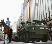 On parade: A police officer on horseback contrasts with an armored Self-Defense Forces vehicle Sunday morning during a disaster drill in the Ginza shopping district in Tokyo. Ahead of Disaster Prevention Day on Monday, Tokyo held several drills with the participation of U.S. military forces and rescuers from South Korea and Taiwan. | KYODO PHOTOS
