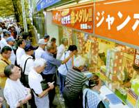 Chasing dreams: A crowd is on hand to buy Summer Jumbo lottery tickets at booths in Tokyo's Ginza shopping district in July.   KYODO PHOTO
