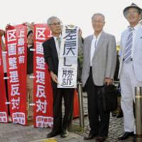 Plaintiffs hold banners Wednesday claiming victory and opposition to rezoning outside the Supreme Court in Tokyo. | KYODO PHOTO